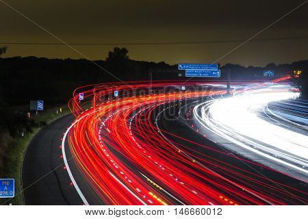 a beautiful picture with lights on the road passing at the speed go the red white wine. cars leave streaks of color