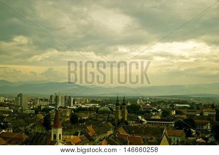 The city of Sibiu in Romania.A medieval city with dramatic atmosphere.Dramatic cloudy sky above the city. There are spires and rooftops and some modern buildings in the distance.