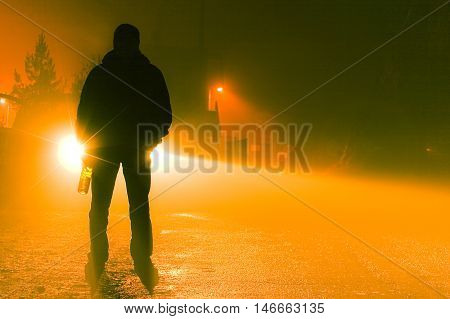 A silhouette of a drunk person standing on the road on a foggy night holding a bottle.