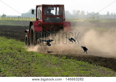 Farmer working the field with tractor in rural landscape.