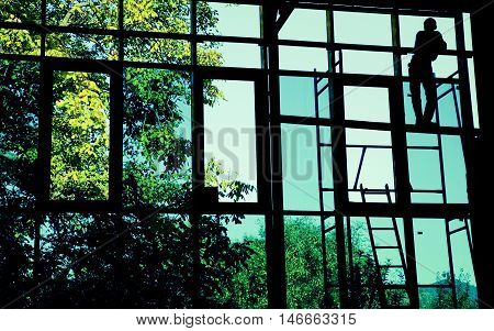 Silhouette of resting worker through large windows.