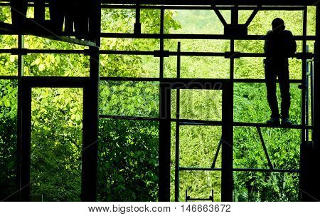 The silhouette of a worker on an open building scaffold. Interior shot looking out onto a forest.