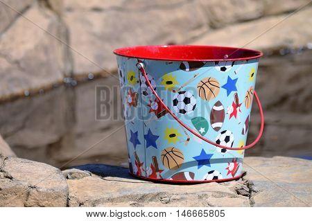 A sport theme pail sitting on a rock