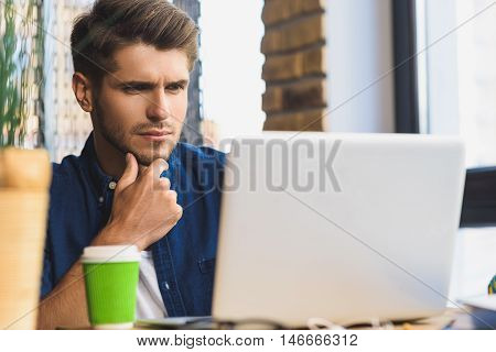 let me think, man sitting in front of laptop with brooding look