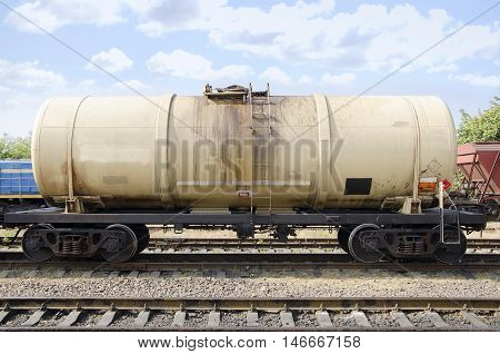 Cargo train with oil tanker. Wagon on station