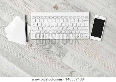 Workstation at a white rustic wooden desk with a mobile phone, computer keyboard and notepad and pen arranged in a line above copy space, overhead view