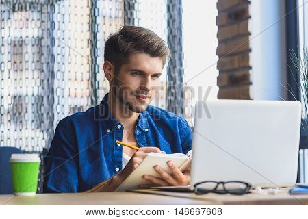 designer drawing while looking into laptop. office backgraund