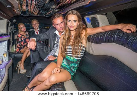 Glamorous Couple With Friends Sitting In Limousine