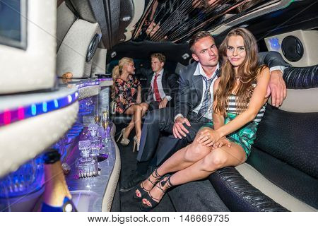 Elegant Young Couple With Friends Talking In Limousine