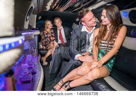 Loving Couple Traveling With Friends In Limousine