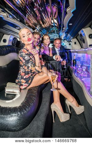 Young Woman Blowing Kiss While Friends Partying In Limousine