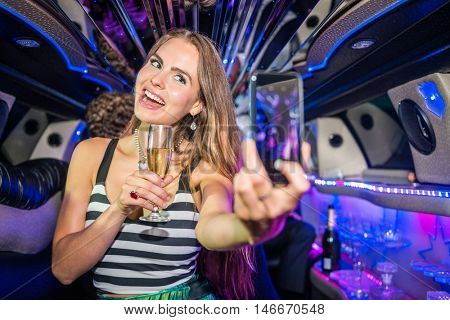 Smiling Woman With Champagne Flute Taking Selfie In Limousine