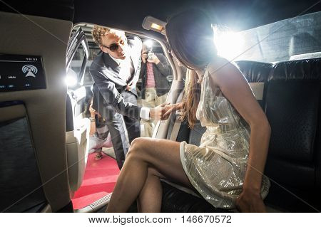 Famous jet set couple getting out of a limousine during a red carpet event, surrounded by the tabloids and paparazzi photographers