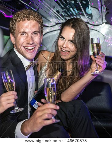 Rich couple drinking champagne in a limousine, having an extravagant party.