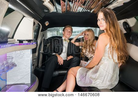 Glamorous Woman Sitting With Friends In Limousine