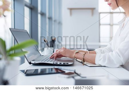 Side view portrait of woman working in home-office as teleworker, typing and surfing internet, having work day