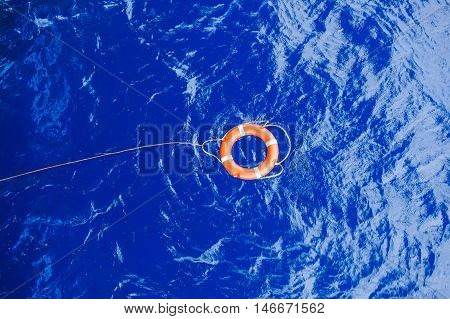 Life buoy bound with rope rescue floating in the blue sea.