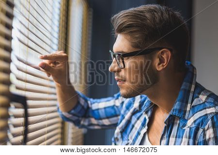 half face of curious guy in glasses spying thru jalousie