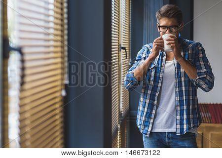 satisfied worker drinking tea in front of jalousie