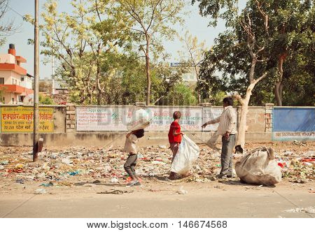 JAIPUR, INDIA - JAN 21, 2015: Unidentified children with poor father clean out debris for further recycling process on January 21, 2015. Jaipur with population 6664000 people is a capital of Rajasthan