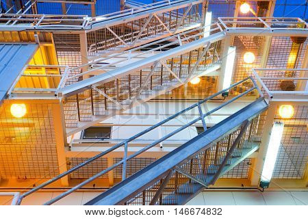 fire escape ladder upper view on offshore platform with lighting in evening.