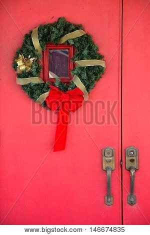 A Christmas wreath hanging on a bright red door with two large gold handles.