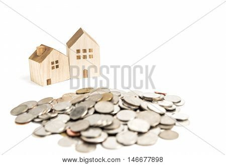 Wooden house model with pile of coin. Selective focus on house model. House finance concept.