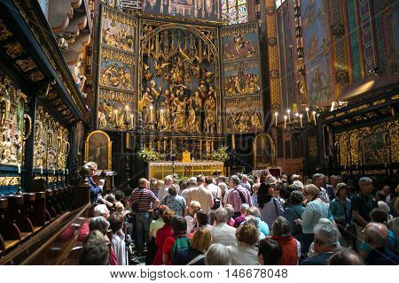 POLAND, KRAKOW - MAY 27, 2016: Tourists and pilgrims in anticipation of the opening of the main altar of the medieval St Mary's church in Krakow. St. Mary's Church was built in the XIII-XIV century.
