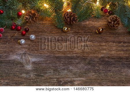Christmas border with fir tree and lights on old wooden background