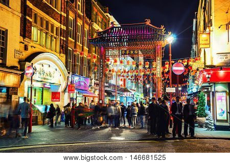 LONDON UK - AUGUST 29 2014: Chinatown at night illuminated signs. Traditional arch at Gerrard street. Blurred people various cafes bars and restaurants