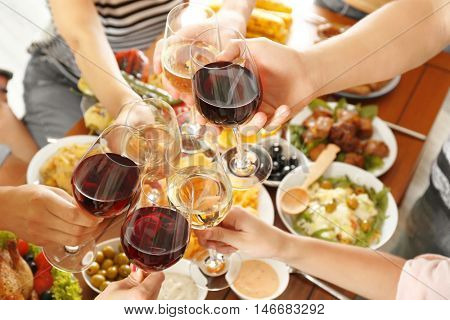 Friends cheering with glasses of wine in restaurant