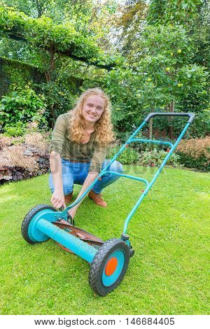 Young caucasian woman reparing lawn mower on green grass