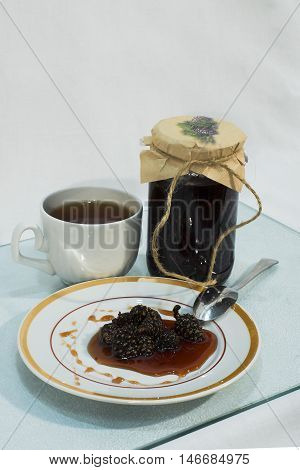 Jam made from pine cones on a plate and a cup of tea