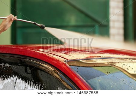Serviceman cleaning car using high pressure water
