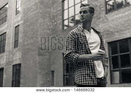 Thinking about importance. Black-white shot of young man looking away thoughtfully and take away coffee while walking in city