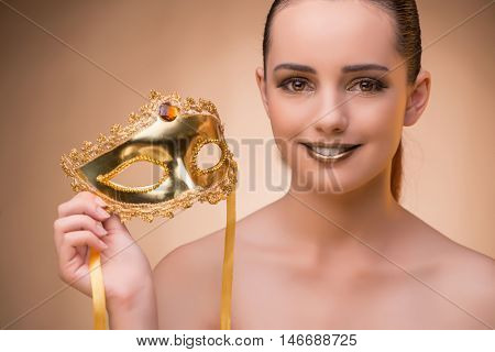 Young woman with mask in carnival concept
