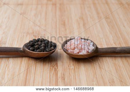 Salt And Pepper Seasonings Of Pepper Corns And Rock Salt On Wooden Spoons