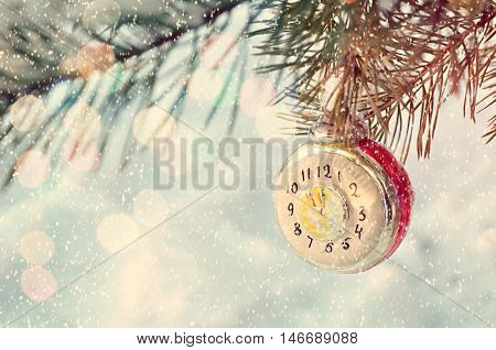 New Year and Christmas background -New Year Christmas toy on snowy fir tree branch. New Year festive card with bokeh and showfall. Christmas and New Year background. Focus at the clock.Shallow DOF.