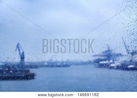 A dull rainy day in Hamburg with raindrops on a window, behind which the blurry harbor is visible out of focus.