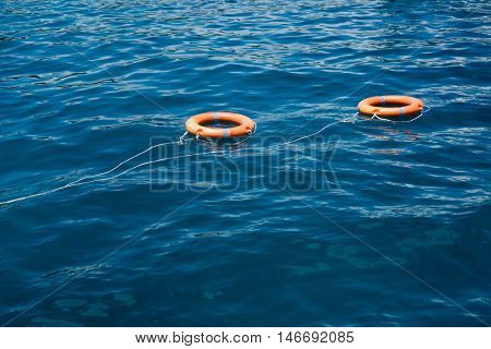 Two bright orange life buoy floating on the surface of blue water in the sea