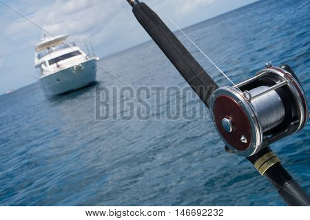 Fishing rod on a boat over blue sky and white sailing boat in the sea. Picture of fishing rod in pole holders on the back of a boat