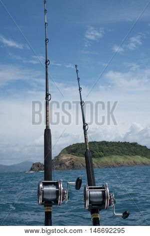Fishing rods on a boat over blue sea, sky and green island. Picture of two fishing rods in pole holders on the back of a boat