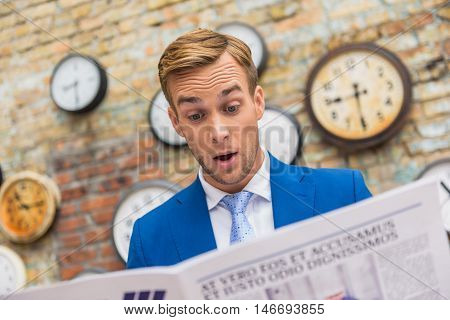 Getting updated on local news. Close up of surprised businessman reading news, looking at newspaper with brick wall on background