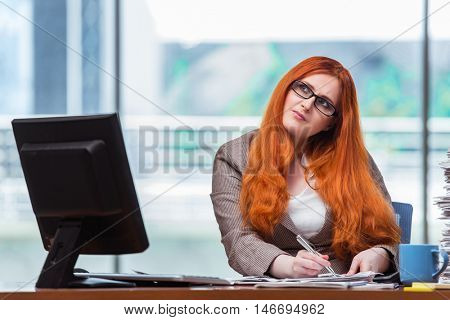 Redhead businesswoman sitting at her desk in the office