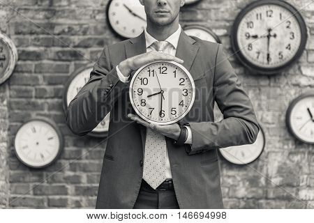 Time to get going. Cropped black-white shot of businessman in suit holding wall clock in front of him and posing for camera
