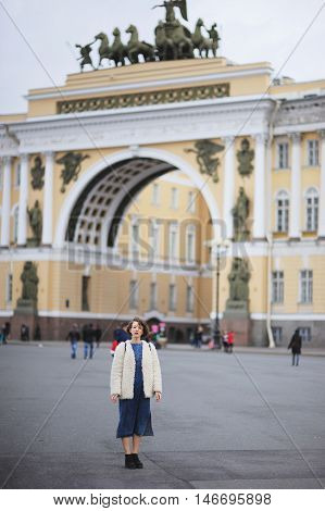 Young beautiful girl student in a blue denim dress and white jacket standing on Palace Square near the Arc de Triomphe of the Head of Staff in St. Petersburg