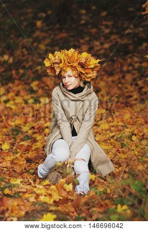 Young beautiful smiling girl with a crown of autumn maple leaves sitting on fallen leaves in the forest.
