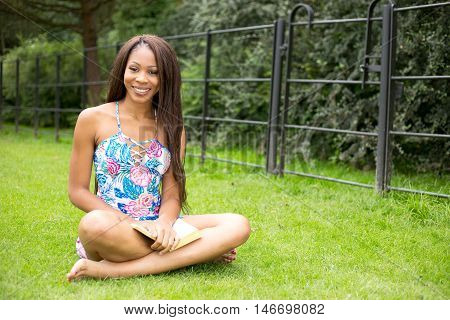 young woman sitting in the park with a book