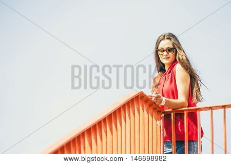 Young long haired girl with sunglasses leaning against railing on the urban bridge. Lifestyle funky in summer. Trendy cool sport teen.