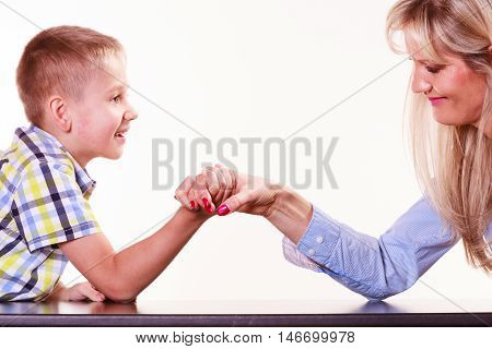 Spending time with family fun and family bonds. Mother and son arm wrestle and have fun indoors.